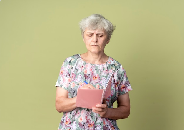 自信を持って年配の女性は、オリーブグリーンの壁に隔離された何かを書き留めるノートとペンを保持します。