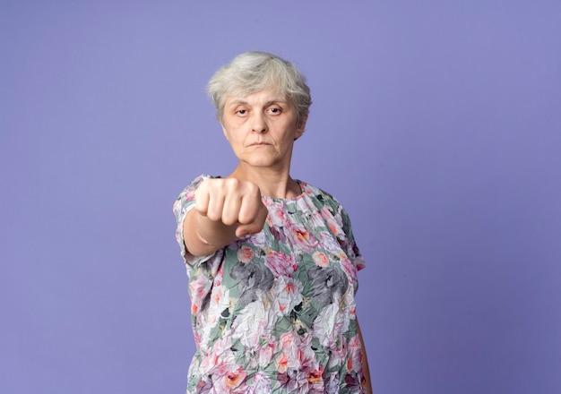 Уверенная пожилая женщина протягивает кулак на фиолетовой стене