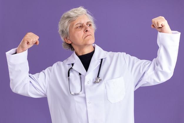 청진기가 있는 의사 제복을 입은 자신감 있는 할머니는 옆구리를 보고 있는 팔뚝을 긴장시킵니다.