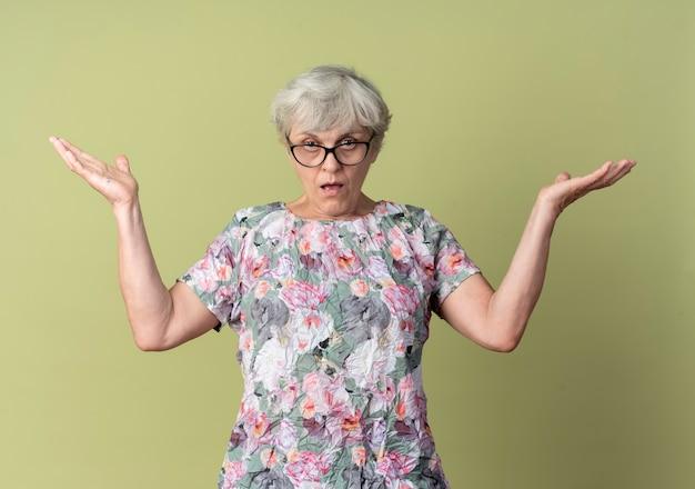 光学メガネで自信を持って年配の女性がオリーブグリーンの壁に孤立して見える手を上げる