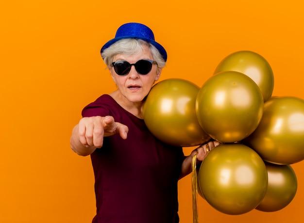 파티 모자를 쓰고 태양 안경에 자신감이 노인 여성은 오렌지 벽에 고립 된 전면을 가리키는 헬륨 풍선 스탠드