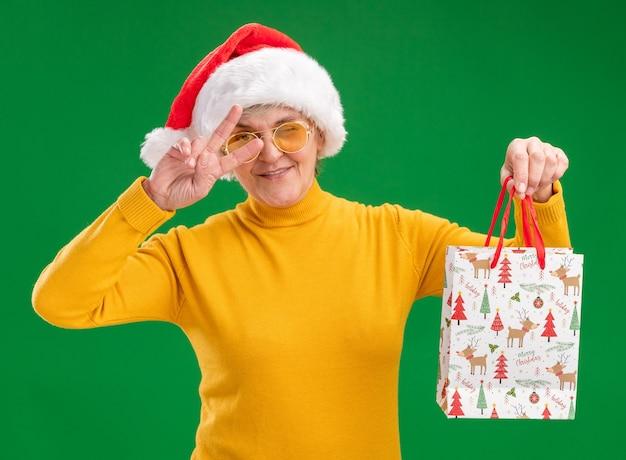 Уверенная в себе пожилая женщина в солнцезащитных очках в шляпе санта-клауса моргает и держит бумажный подарочный пакет, жестикулируя знак победы, изолированный на зеленой стене с копией пространства