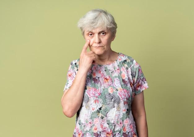 自信を持って年配の女性がオリーブグリーンの壁に隔離された目を指しています