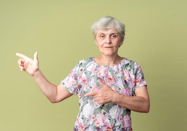 自信を持って年配の女性は、オリーブグリーンの壁に分離された両手で横を指しています