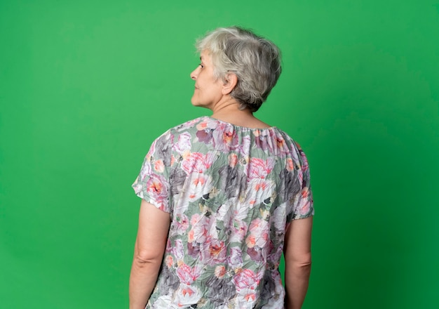 Confident elderly woman stand looking at side, back view, isolated on green wall