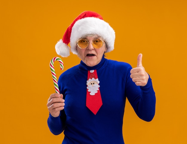 Confident elderly woman in sun glasses with santa hat and santa tie holds candy cane and thumbs up isolated on orange wall with copy space