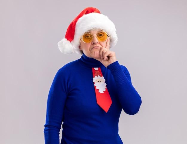 La donna anziana sicura in occhiali da sole con il cappello di babbo natale e la cravatta di babbo natale mette la mano sul mento isolato sulla parete bianca con lo spazio della copia