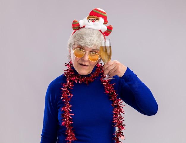 Fiduciosa donna anziana in occhiali da sole con fascia santa e ghirlanda intorno al collo tenendo un bicchiere di champagne isolato su sfondo bianco con spazio di copia