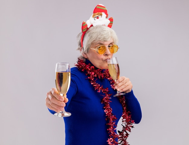 Fiduciosa donna anziana in occhiali da sole con santa fascia e ghirlanda intorno al collo tiene e beve bicchieri di champagne