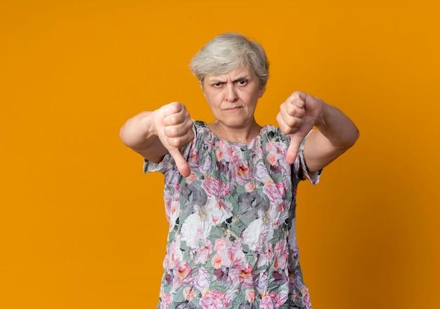 Уверенная пожилая женщина показывает палец вниз двумя руками, изолированными на оранжевой стене
