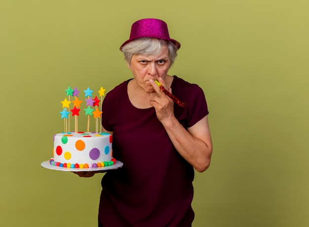 Confident elderly woman wearing party hat blowing whistle holding birthday cake isolated on olive green wall with copy space