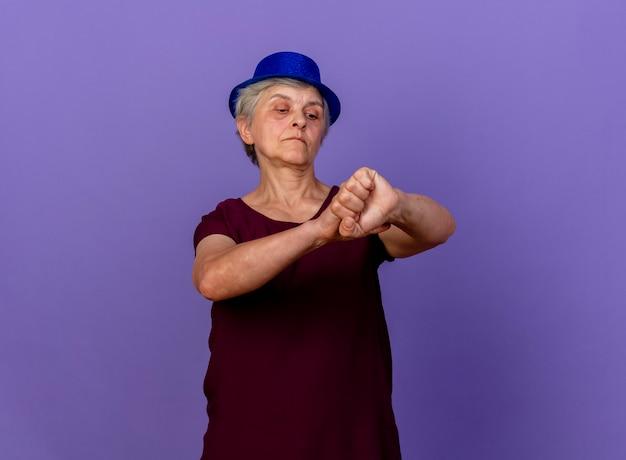 파티 모자를 쓰고 자신감이 노인 여성이 보유하고 보라색 벽에 고립 된 팔을 찾습니다