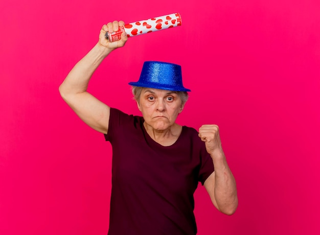 Confident elderly woman wearing party hat holds confetti cannon and keeps fist on pink