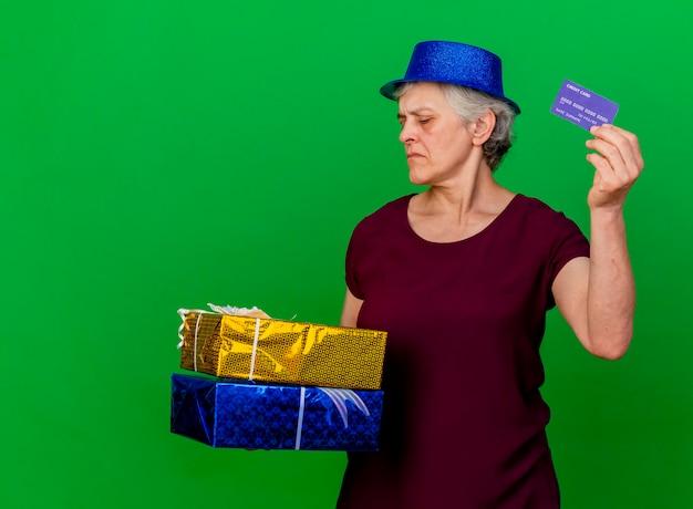 La donna anziana sicura che porta il cappello del partito tiene i contenitori di regalo e la carta di credito sul verde