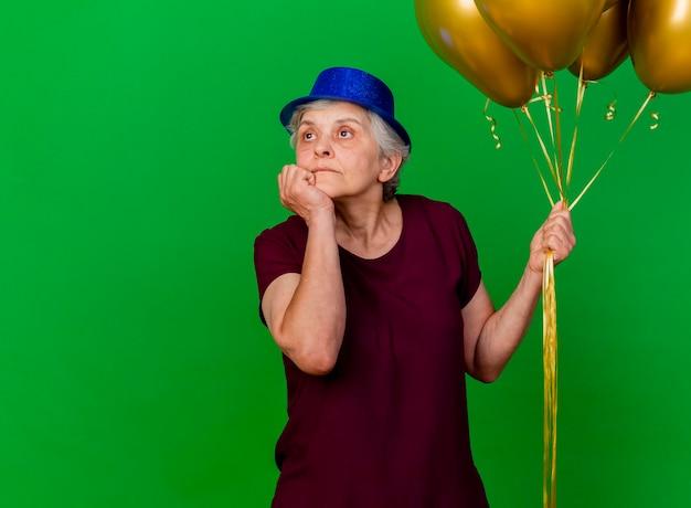 パーティーハットをかぶって自信を持って年配の女性は、ヘリウム気球を保持し、緑の側を見てあごに手を置きます