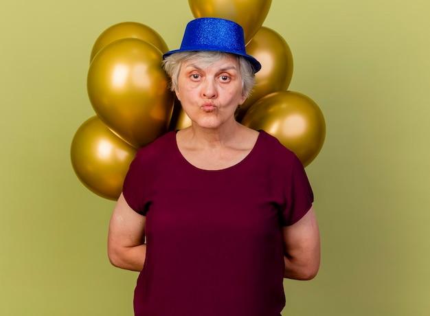 Уверенная в себе пожилая женщина в шляпе для вечеринки держит за спиной гелиевые шары на оливково-зеленом
