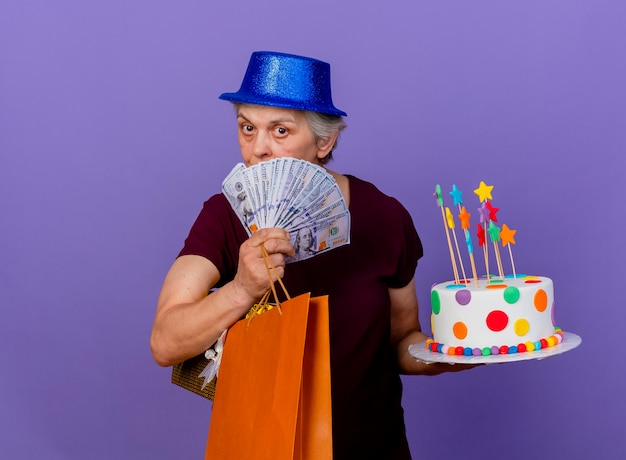 La donna anziana sicura che porta il cappello del partito tiene i sacchetti della spesa di carta dei soldi e la torta di compleanno isolata sulla parete viola con lo spazio della copia