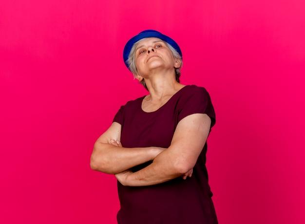 パーティーハットを身に着けている自信を持って年配の女性はピンクの腕を組んで立っています