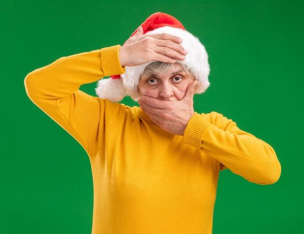Fiduciosa donna anziana con santa hat mette la mano sulla bocca e sulla fronte isolato su sfondo viola con copia spazio