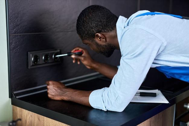自信のある電気技師、修理、キッチンのコンセントの設置。ドライバーが作動し、修理している全体的なツイストソケットのマンマスター。住宅用電気システムのプラグ電気に取り組んでいる男性