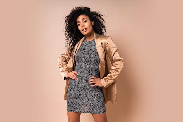Fiduciosa donna elegante con pelle scura e incredibili capelli ricci in vestito splendente da festa e giacca di raso in posa.