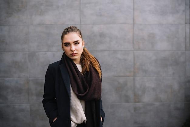 Giovane donna elegante sicura in cappotto con la sciarpa vicino alla parete grigia