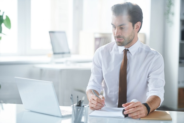 Confident employee making notes while watching online video in front of laptop in office