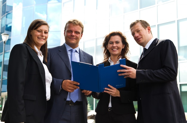 Confident employees discussing document at meeting