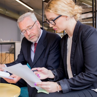 Confident employees discussing papers at meeting