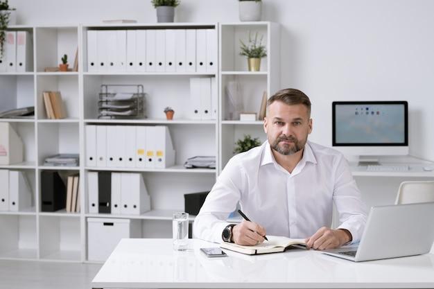 彼のオフィスに座って、ノートにメモを取りながら仕事を整理する白いシャツを着た自信のある雇用主