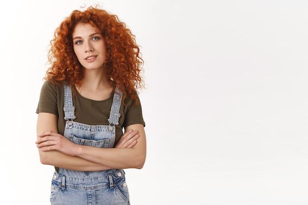 自信を持って力を与えられた見栄えの良い赤毛の縮れ毛の女の子、腕を組んで、カメラに自信を持って笑顔で、彼女の仕事を知って、プロの雰囲気を与え、野心的で、断固とした勝利を収めます