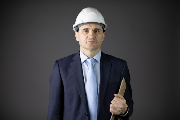 Confident engineer in helmet and formal clothing holds clipboard looks at camera