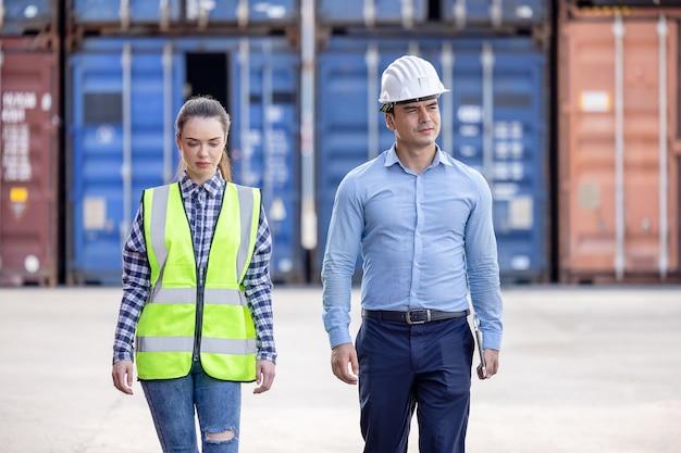 Уверенный портрет инженеров в униформе, стоящих перед контейнерами.