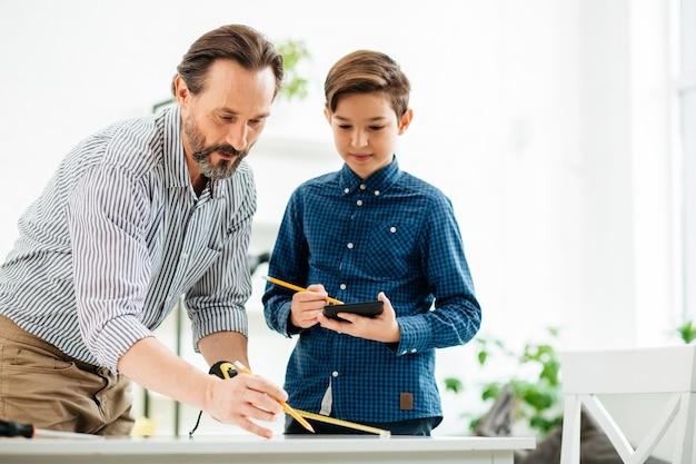 自信を持って熱狂的な中年男性が息子の学校のプロジェクトを手伝い、テーブルで巻尺を使用する