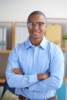 Confident entrepreneur looking at camera with arms folded smiling