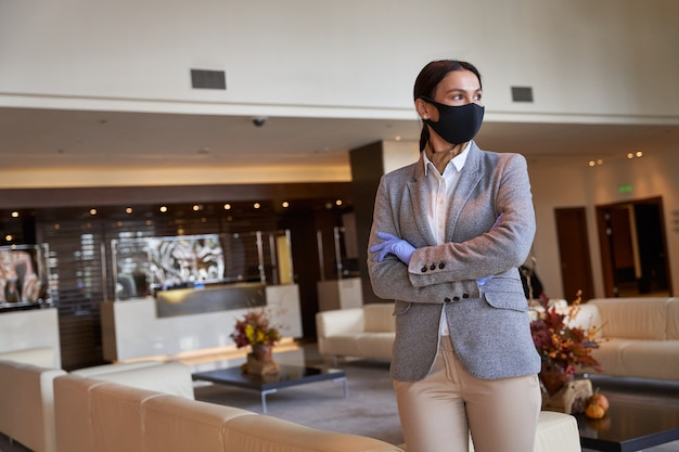 Confident entrepreneur standing alone in a lobby and looking into the distance. fabric mask on her face