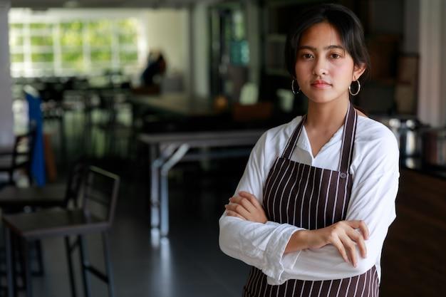 Уверенно этническая официантка женского пола в фартуке, стоящая со скрещенными руками в кафе и смотрящая на камеру.