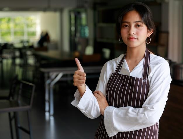 Уверенно этническая официантка женского пола в фартуке стоя с большим пальцем руки вверх в кафе и смотря камеру.