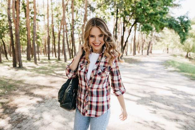 Ragazza europea sicura che cammina nel parco con lo zaino. colpo all'aperto della romantica signora bionda indossa una camicia a scacchi in primavera.