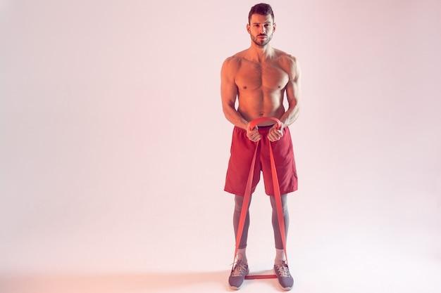 Уверенный европейский спортсмен делает упражнения с лентой сопротивления. молодой красивый бородатый мужчина с обнаженным спортивным торсом. изолированные на бежевом фоне. студийная съемка. копировать пространство