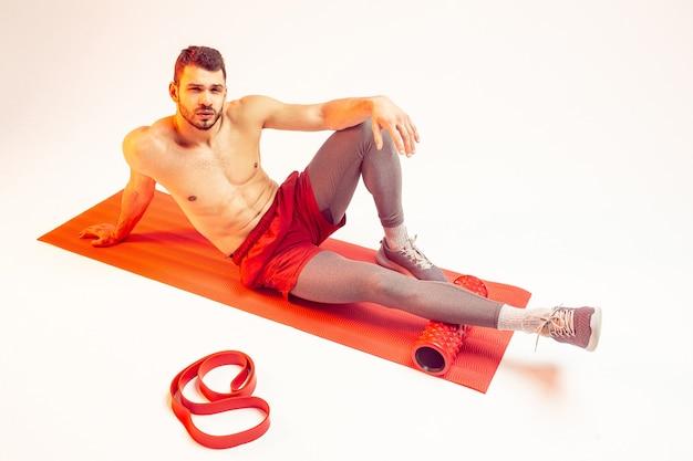 Уверенно европейский спортсмен, сидящий на фитнес-коврике с массажным роликом. молодой красивый бородатый мужчина с обнаженным спортивным торсом. изолированные на бежевом фоне. студийная съемка. копировать пространство