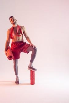 Уверенный в себе европейский спортсмен с эспандером, фитнес-ковриком и массажным роликом. молодой красивый бородатый мужчина с обнаженным спортивным торсом. изолированные на бежевом фоне. студийная съемка. копировать пространство