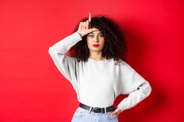 Уверенная европейская женщина с вьющимися волосами, издевающаяся над заблудшей командой, демонстрируя жест неудачника и безразлично глядя в камеру, стоя в повседневной одежде на красном фоне.