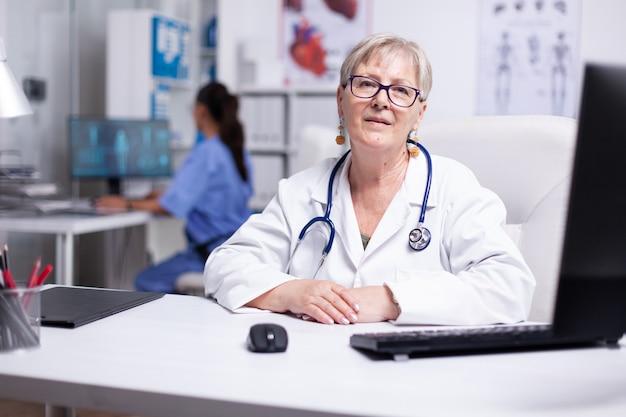 Уверенно опытный старший врач в белом халате со стетоскопом, который проводит видеоконференцию и консультирует партнеров или пациентов, глядя в камеру. врач консультирует пациента с помощью видеозвонка