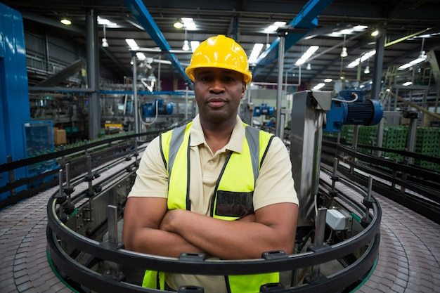 Confident factory worker standing near the conveyor belt