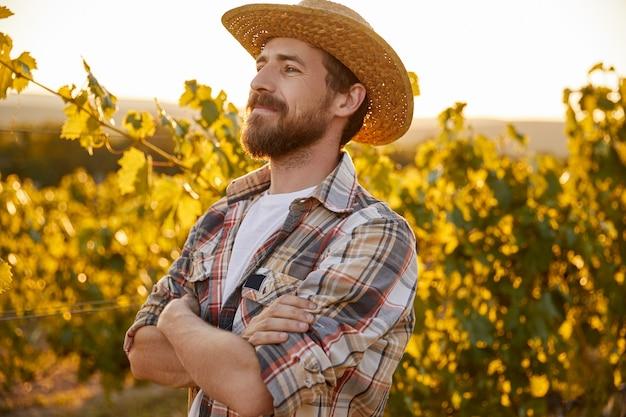 Confident farmer standing near grapevine