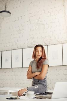 새로운 패브릭 샘플을 확인하는 랩톱에서 작업하는 그녀의 작업 환경에서 자신감있는 패션 비평가.