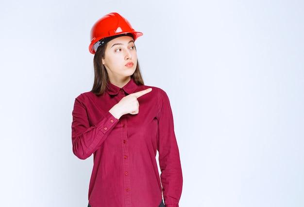 赤いヘルメットをかぶって立って指さしている自信のある女性建築家。