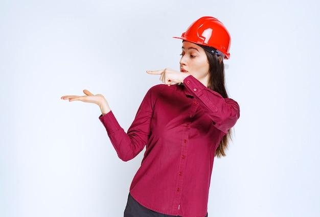 서서 가리키는 빨간 헬멧을 쓴 자신감 있는 여성 건축가.