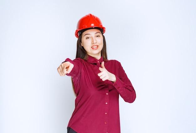 白い壁の上に立ってポーズをとって赤いヘルメットをかぶった自信のある女性建築家。